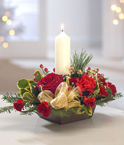 Christmas candle, with a white ribbon, red rose and an assortment of small red flowers