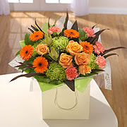 A bouquet of orange and pink roses with orange daisies