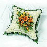 A floral cushion, white, orange open tulips at the centre