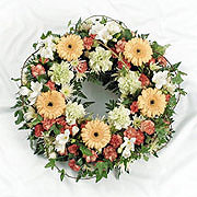 A large floral wreath, adorned with white, orange and red flowers