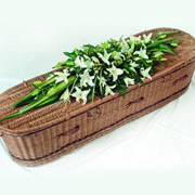 A wicker coffin spray, with white tulips on top of the coffin