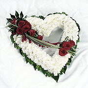 A large, heart shaped, posy, adorned with red roses