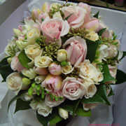 A bouquet of spray cream roses, Sedum, Freesia, pale pink roses and tulips