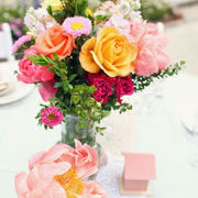 A table centre bouquet of orange, yellow, pink roses and white daisies